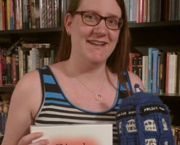 Picture of Jen Desmarais in front of bookcases. She is holding her game Blush and the crocheted TARDIS. She is 3 days overdue, but the bump is hidden by the objects.
