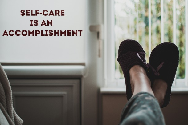 ID: Living space with window. Feet up in a relaxed position, clad in warm slippers.  Text reads: Self-care is an accomplishment