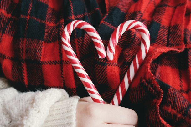 ID: Person in red and black plaid shirt and white sweater, holding two candy canes in the shape of a heart.
