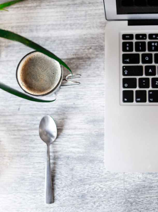 Desktop featuring a cup of coffee, a spoon, and part of a laptop keyboard and screen.