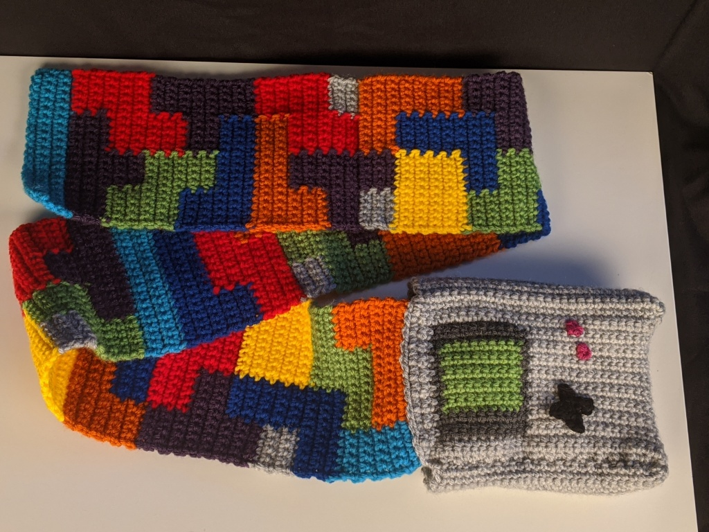 ID: Crocheted pocket scarf with the pocket being a gameboy and the scarf showing Tetris shapes.