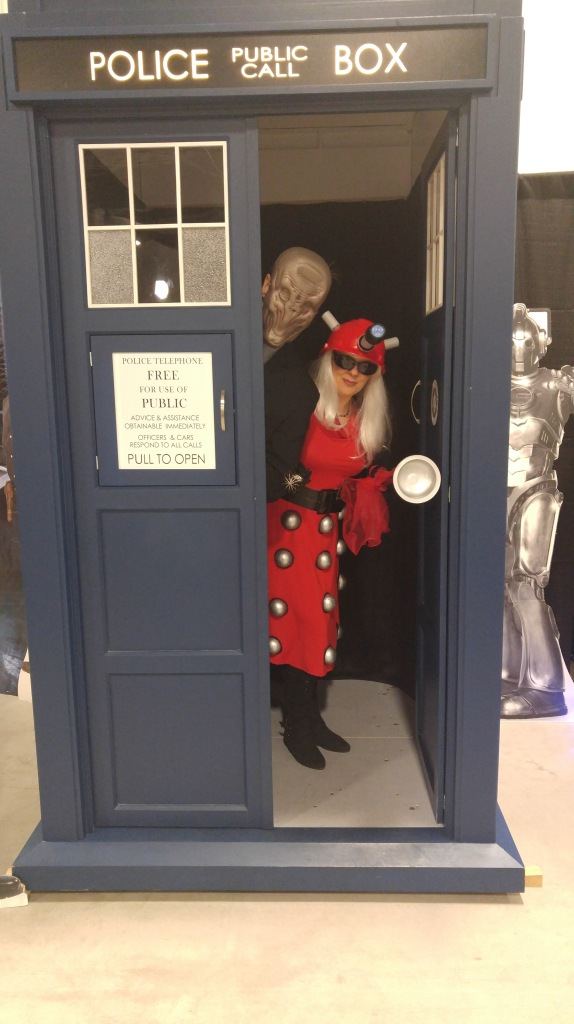 ID: Me, in a TARDIS, dressed as a red fashionista dalke. My husband is dressed like the Silence.