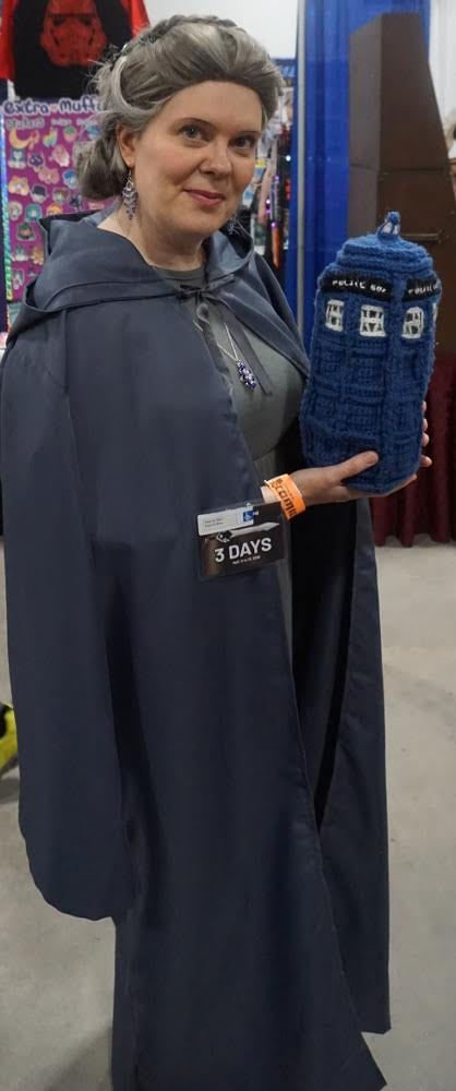 ID: Me, dressed in my General Leia costume, holding the famous crocheted Travelling TARDIS!