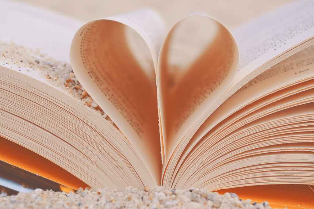 ID: opened white book with the middle pages folded into the shape of a heart.
