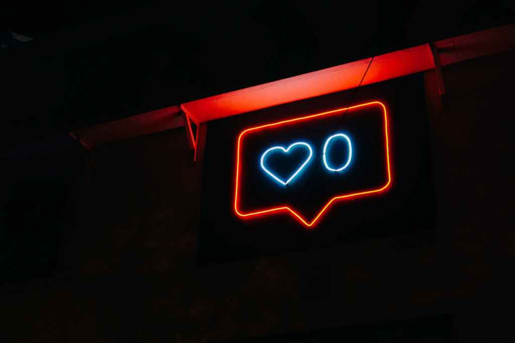 ID: Dark background. A neon sign featuring a heart with zero likes.