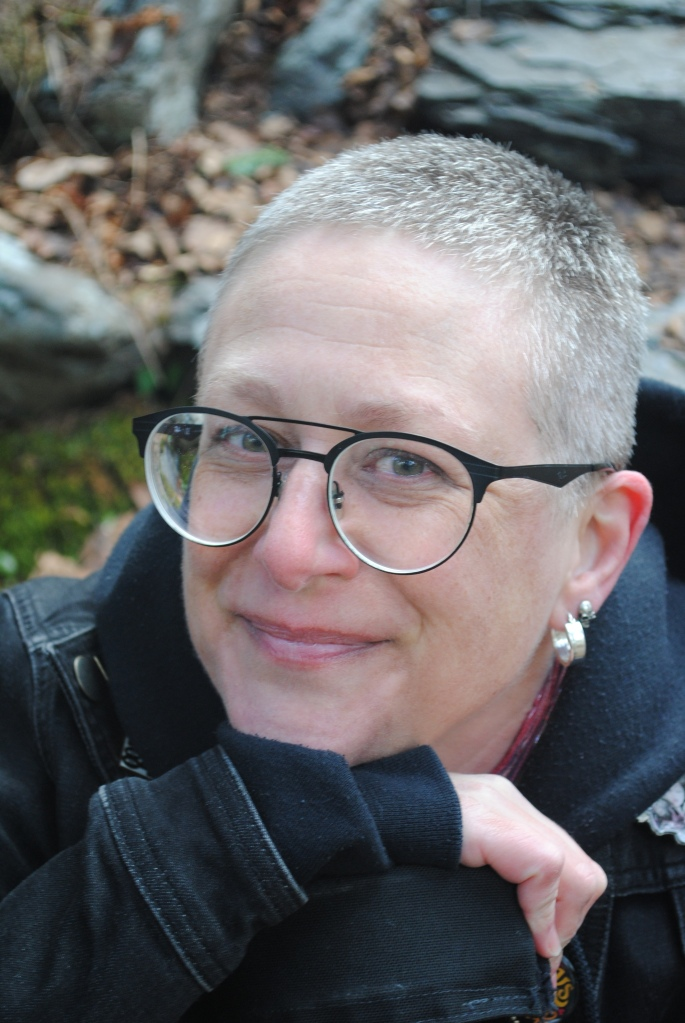 ID: Closeup of Michele Butler Hallett, a white woman with cropped silvery-blonde hair and round black-rimmed glasses. She is dressed in a dark blue hoodie and denim jacket, and is looking at the camera and smiling.